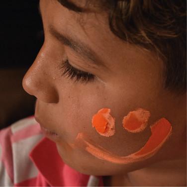 Niño con una cara sonriente naranja pintada en su cara.