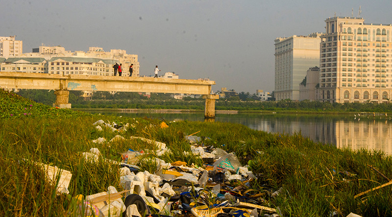 a pile of trash on the banks of the adya