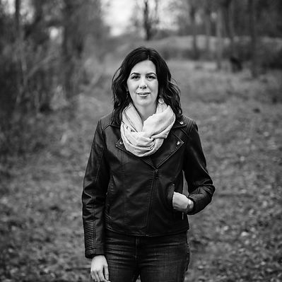 A black and white pitcure of Rachael  standing in a wood. She is a white female with long wavy hair
