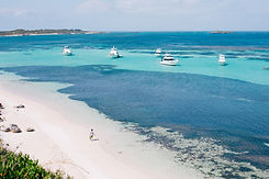 boats out on a blue sea with a white sandy beach.