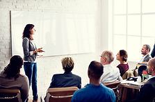 a female teacher standin in front of a white board, delivering a presentation to a group of adults.