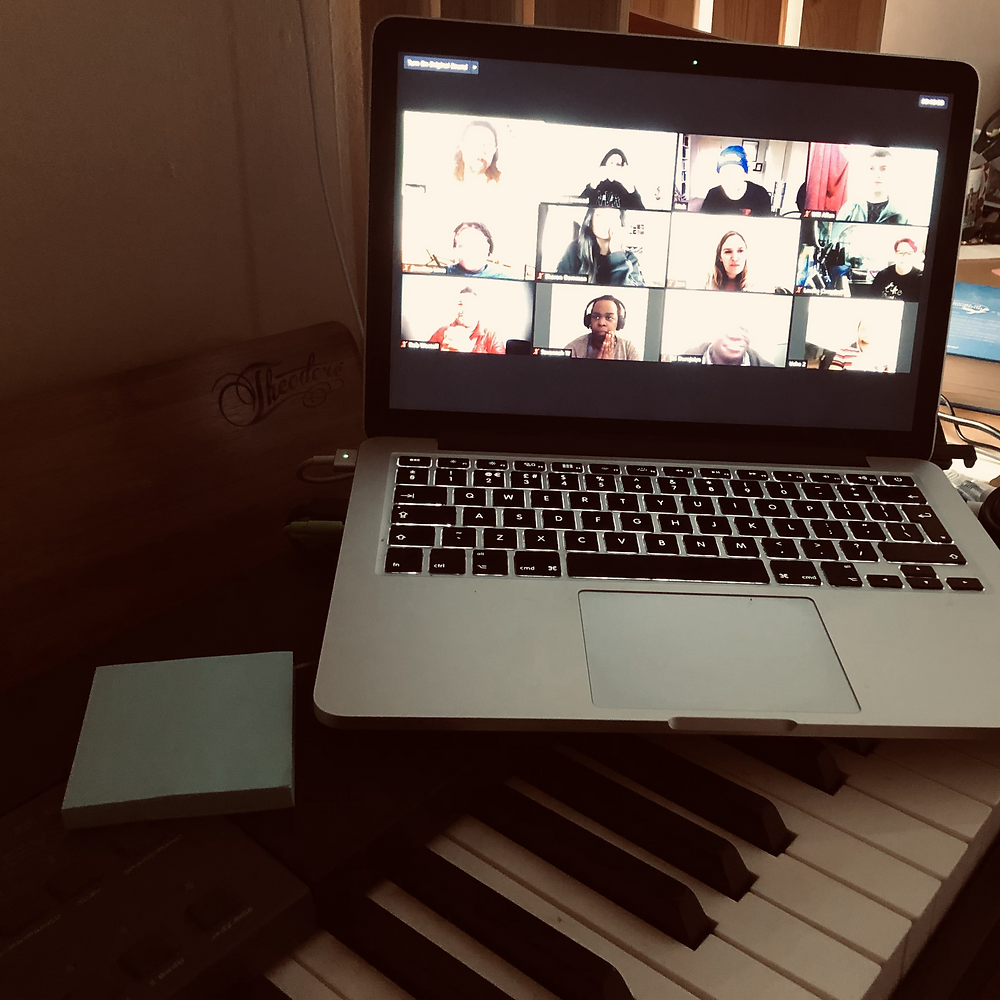 A laptop onto of a musical keyboard, with a gallery of faces on a Zoom call