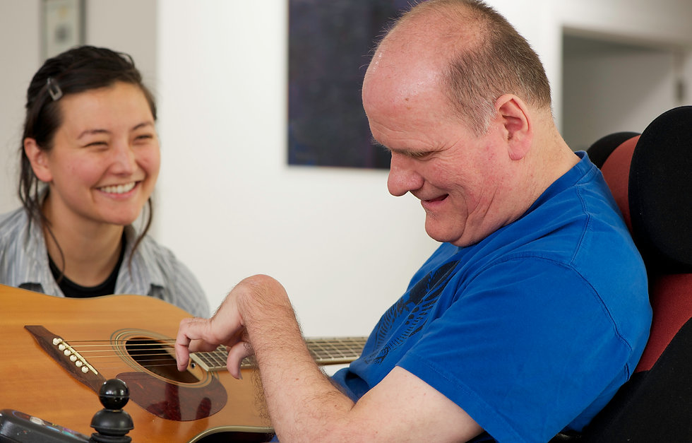 a man in a wheelchair wearing a blue shirt being assisted to play the guitar by a female carer