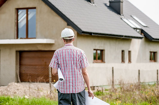 a man with a helmet walking with blueprints towards a house