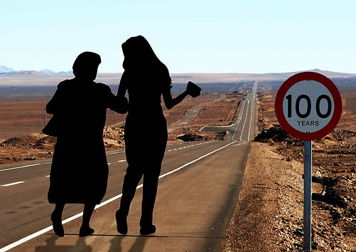 "silhouette of a young woman holding an elderly woman by the hand walking on a long road next to a round traffic sign stating the words ""100 years"""