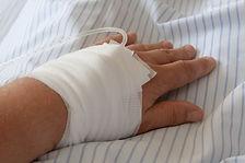 תמונה של יד חבושה עם אינפוזיה על רקע סדי