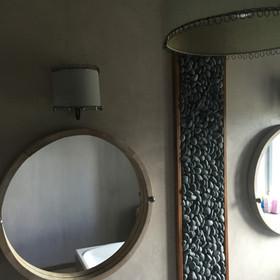 Mur de salle de bain en béton ciré , cadre galets verticaux créé