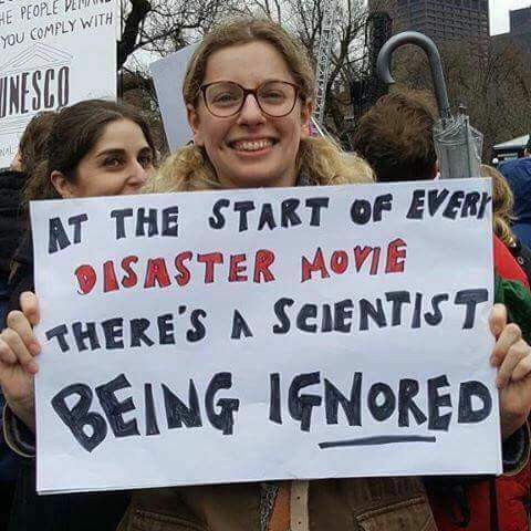 Protester with sign: At the start of every disaster movie there's a scientist being ignored