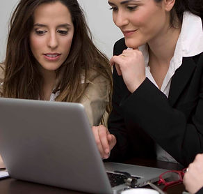two women and a man looking at a laptop computer
