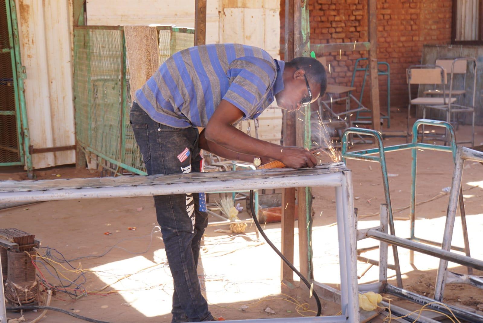 鉄を溶接しながら学習机を修理