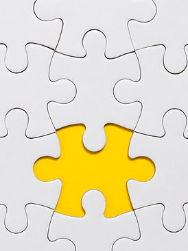 White jigsaw puzzle pieces on a yellow b