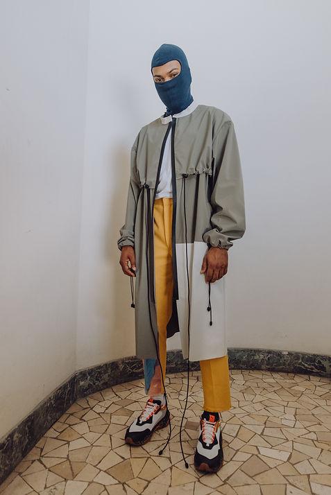 Pantaloni gialli, impermeabile grigio, passamontagna blu