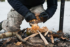 Man starts fire with magnesium fire steel, fire striker. Wood shaving, survival concept..j