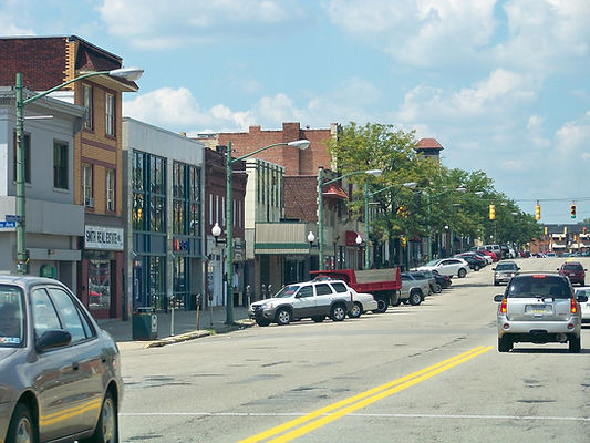 Street in Allegheny county with parked and moving cars, traffic light, Smith Real Estate, and storefronts
