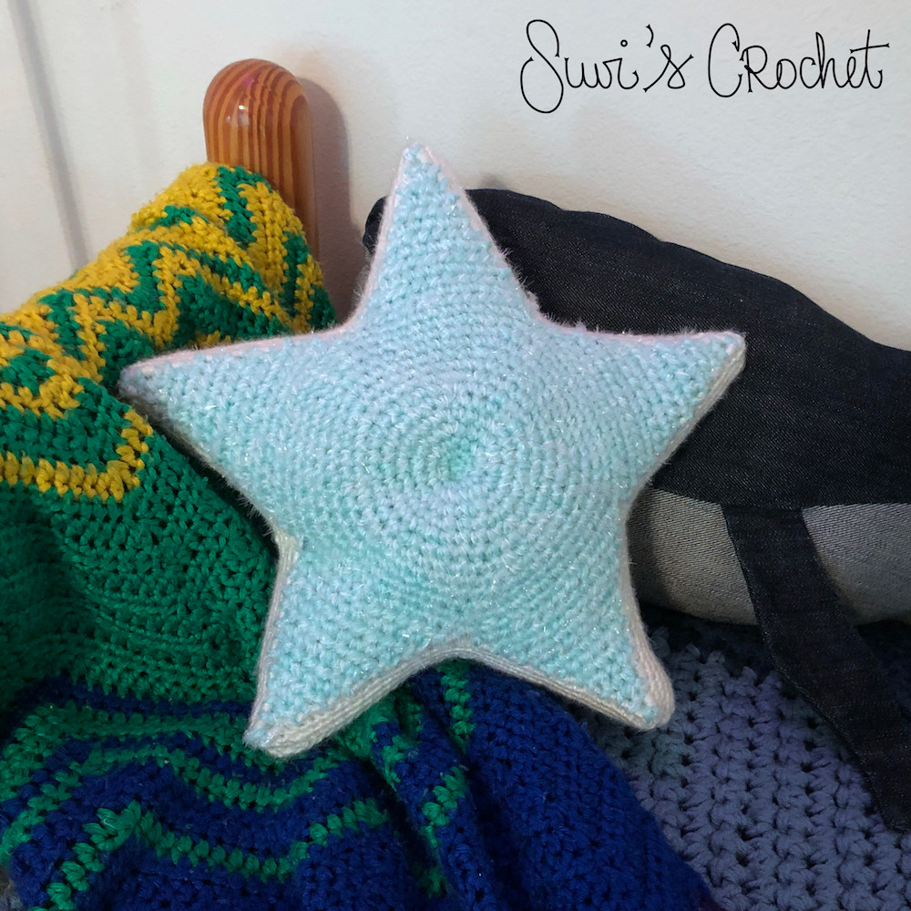 Front of a sparkly star-shaped crocheted pillow.