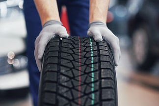 closeup-mechanic-hands-pushing-black-tir