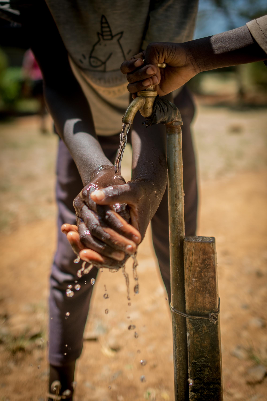 Sauti Kuu- Child washing hands in water
