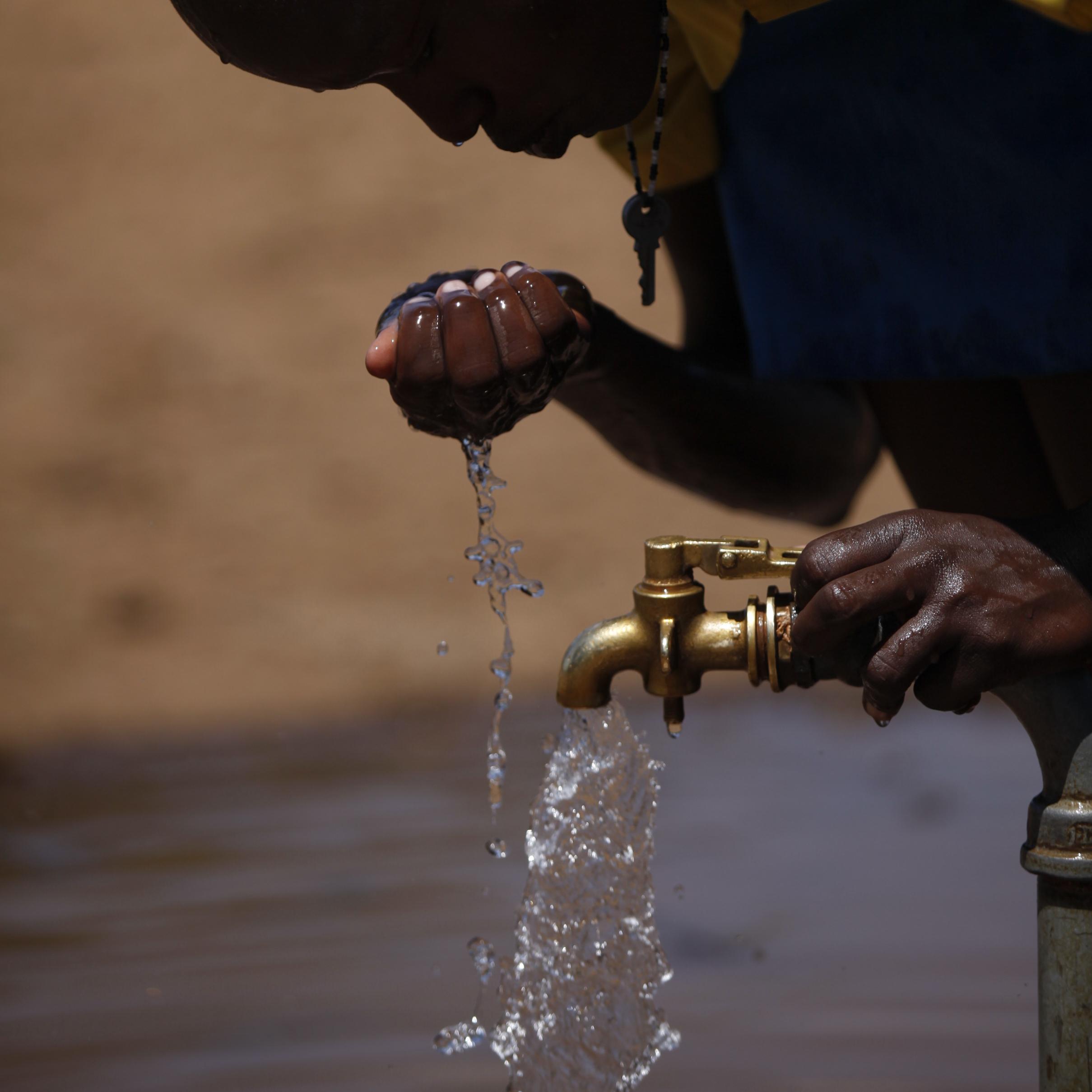 Kenya- little child drinking clean water