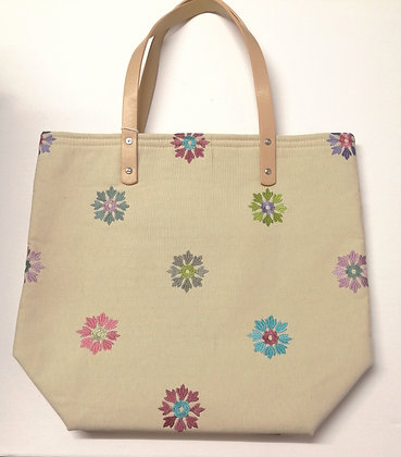 Embroidered medium size shopping bag, leather effect handles.