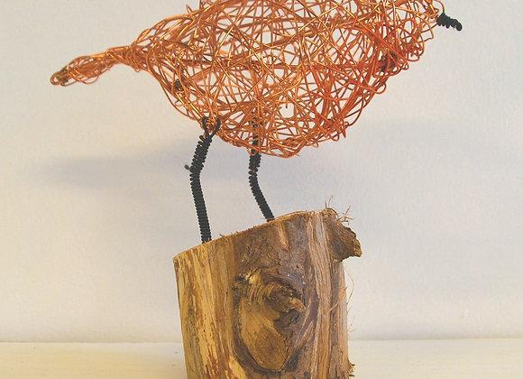 Wire bird in driftwood stand