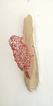 Wire sculpture of bird mounted on wood.