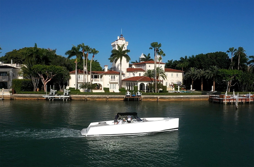 Sleek white boat slows past Carl Fisher's house along Miami's Biscayne Bay