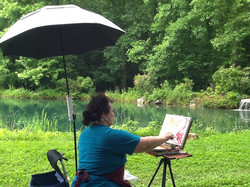 Aleex painting near the pond.