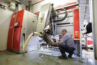 Automation Technician Fixing Robotic Milking Machine