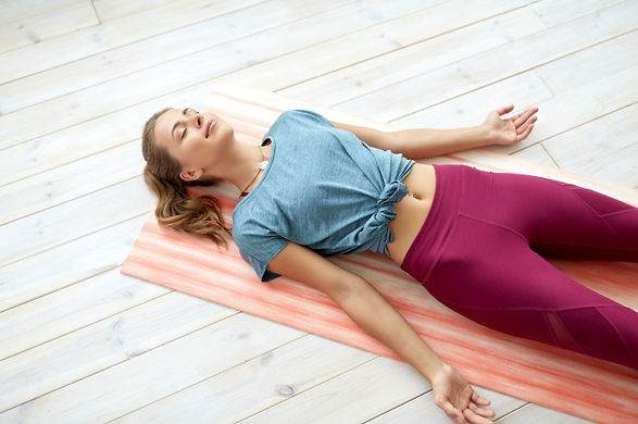 Woman lying down comfortably, practicing a deep relaxation reset and calming her nervous system