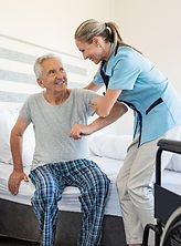 nurse-helping-old-patient-get-up-MJXB65R