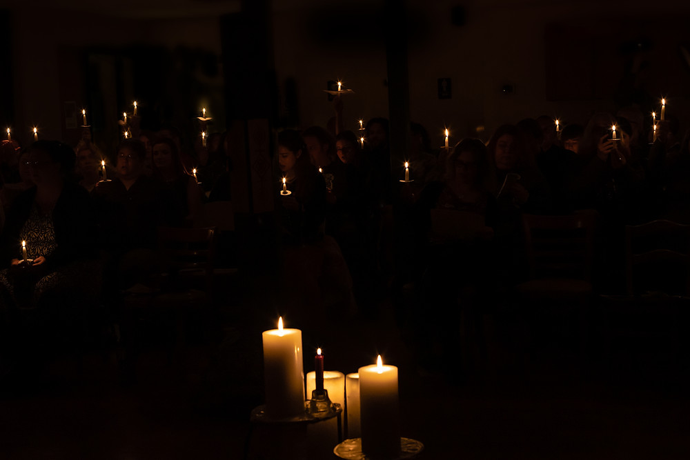 Friends, members, and attendees at Columbia Grove's 2019 Imbolc hold lit candles, and sing praise to Brigid