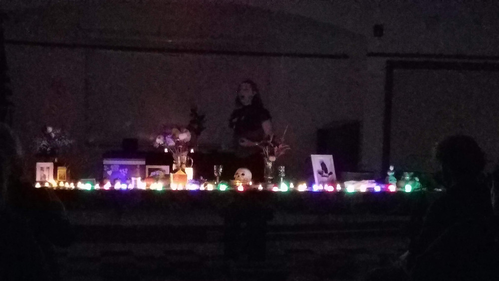 An image of the altar table, lights are turned off, and candles are lit on the table, together with a multi-colored string of skull lights. The altar is decorated with ancestor memorabilia, a well, and an image of a corvid, as well as flowers.