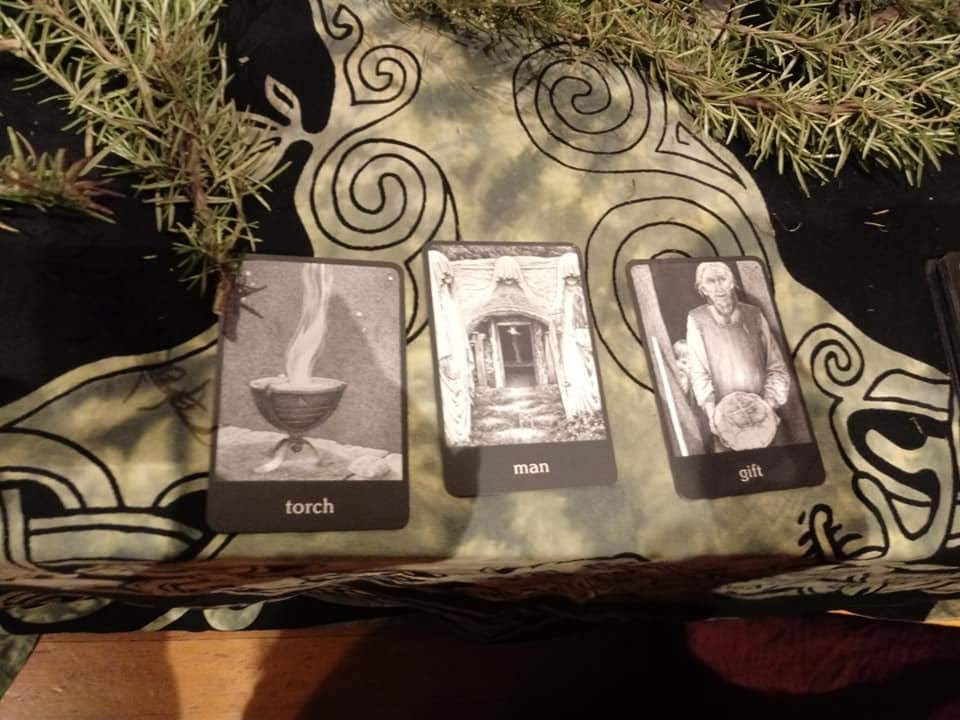 "An altar with three cards in black and white. The first card shows a chalice containing flame, the word ""torch"" The second card shows a representation of three figures, the word ""Man"". The third card shows an elderly figure holding something out, the word ""gift"""