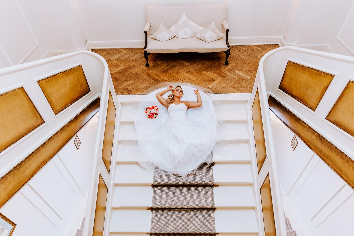 Braut liegt auf den Treppen beim Fotoshooting Europischer Hof