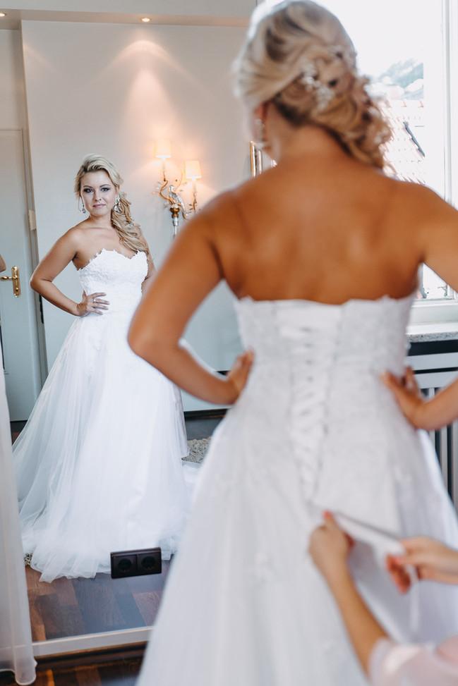 Braut steht vor dem Spiegel beim Getting Ready Hochzeit