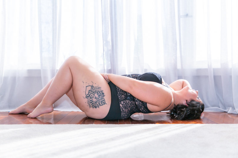 Woman in black teddy lyong on floor.