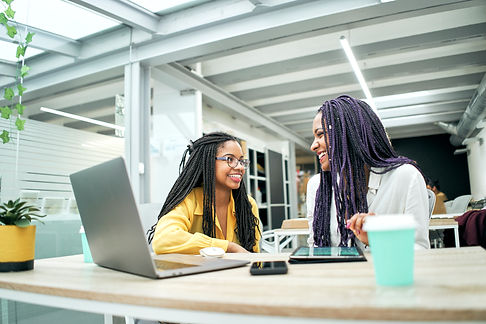 Two smiling business girls in the office, sitting at the table where there is a laptop, a