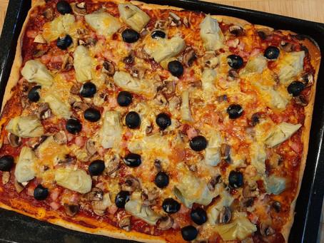 Pizza met ham, salami, artisjok en champignons.