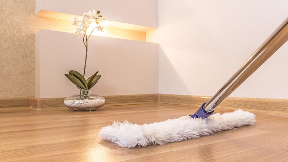 Dust mopping a hardwood floor.
