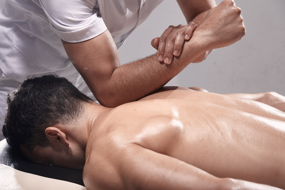 Massage Therapist Massaging Man's Back with Elbow