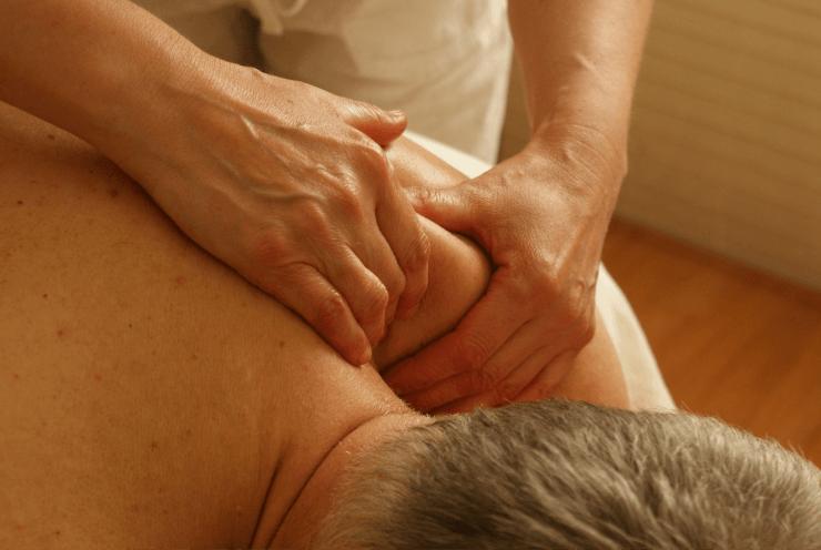 Massage Therapist Massaging Old Man's Back