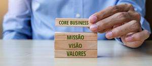 Mão segurando blocos de madeira com inscrição: missão, visão, valores e core business.