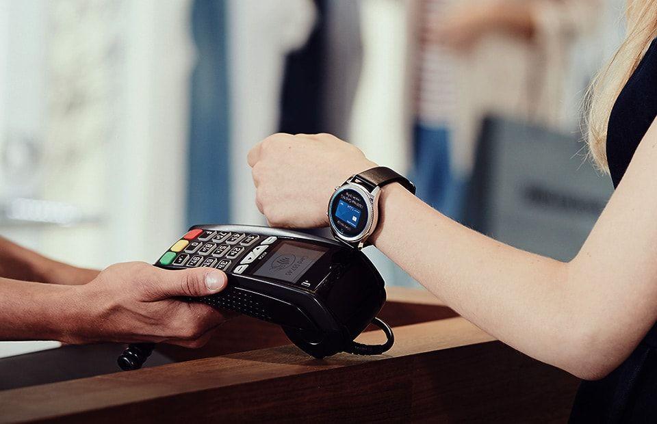 Mulher efetuando um pagamento na maquininha usando um smartwatch.