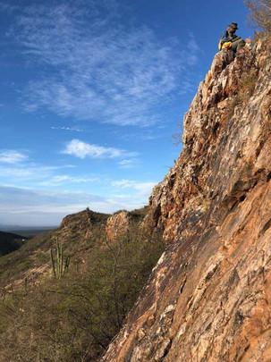 Geologist prospecting a ridgetop outcrop