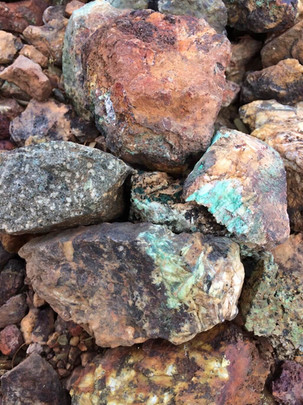 Copper oxides found near resistive weathering structures and monzonite dykes