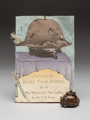 Z 36443, illustrated book 'Japanese Fairy Tale Series No. 16 The Wonderful Tea-Kettle' by Mrs T H James, and 1943.106, 'netsuke of a badger-kettle: the shape-shifting tanuki from the folk take Bunbuku chaguma', Japan