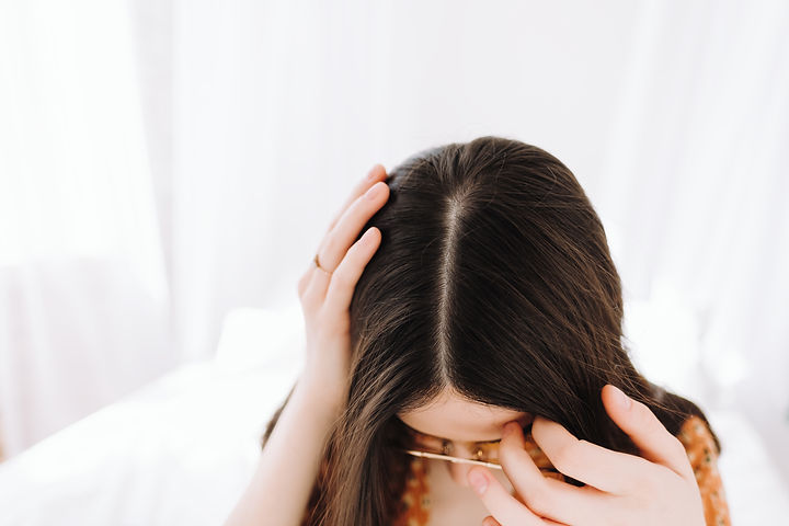 Young brunette woman showing her scalp,