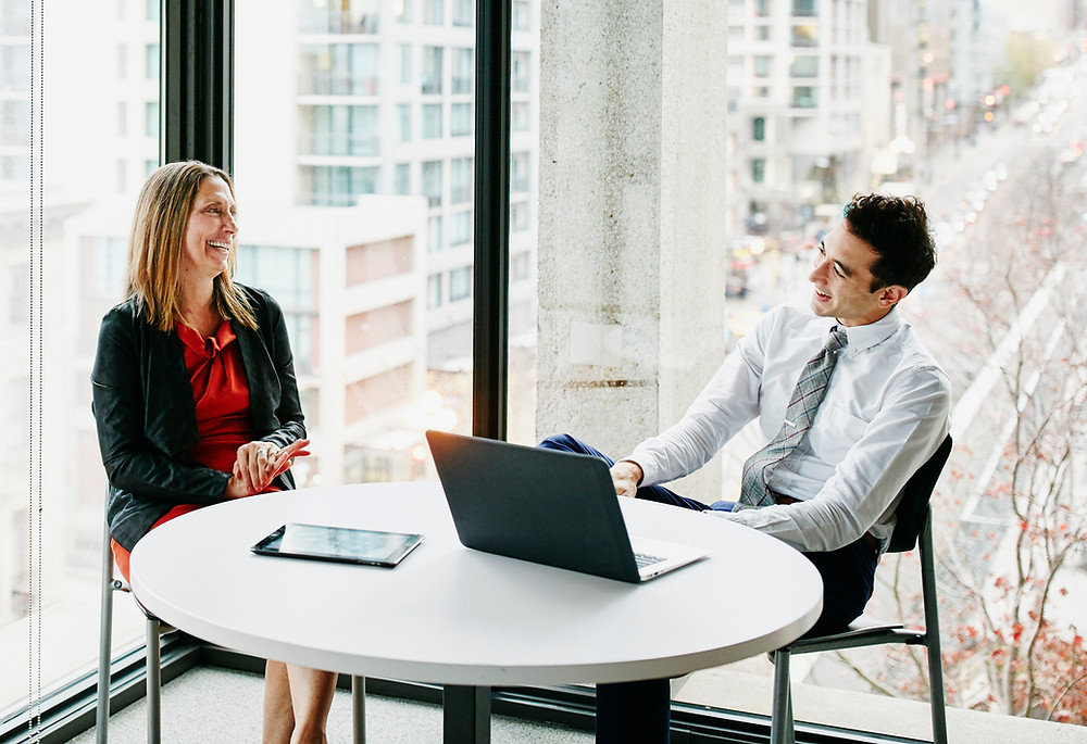 Man interviewing woman for job in front of large window
