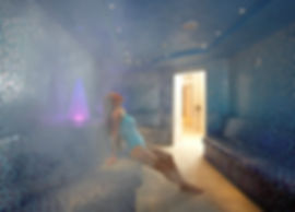 a foggy steam room with a woman in a blue swimming costume relaxing and leaning back on the seat the steam room has blue tiles and small spotlights