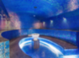 A ver large blue tiled steam room with brigh white lights and curved seating